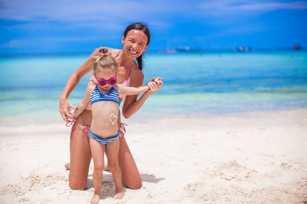 Young beautiful mother and her adorable little daughter have fun at tropical beach Premium Photo