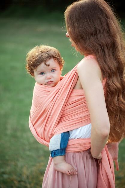 Giovane bella madre che abbraccia il suo piccolo figlio del bambino contro l'erba verde. donna felice con il suo bambino in una giornata di sole estivo. famiglia che cammina sul prato. Foto Gratuite