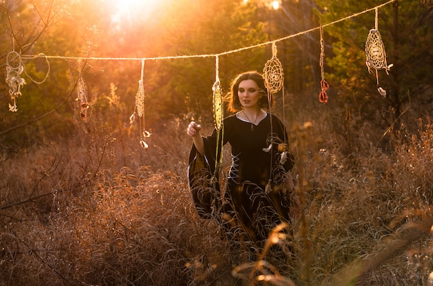 Young beautiful and mysterious woman in black long dress near dream catchers in sunset forest. female silhouette through the sun rays Premium Photo