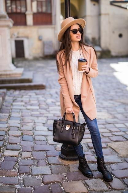 ハンドバッグと一杯のコーヒーが付いている通りに沿って歩く若い美しいきれいな女性。 無料写真