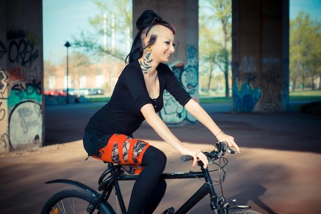 Young beautiful punk dark girl riding bike | Premium Photo