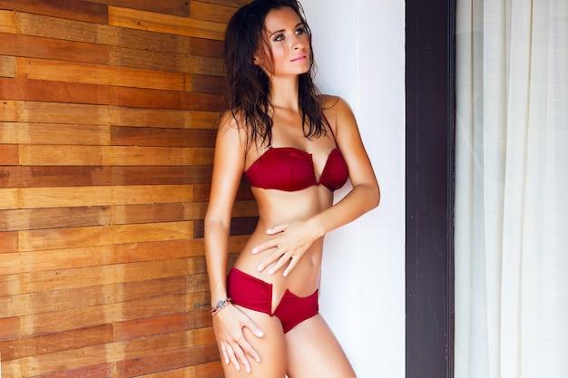 완벽한 몸매를 가진 젊은 아름다운 매혹적인 여자, 럭셔리 빌라에서 섹시한 비키니 포즈, 그녀의 휴가에 편안하고 젖은 머리카락과 밝은 메이크업이 있습니다. 무료 사진