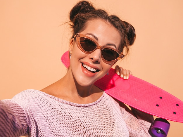 Young beautiful sexy smiling hipster woman in sunglasses.trendy girl in summer knitted cardigan.female with pink penny skateboard,isolated on beige wall.taking selfie self portrait photos on phon Free Photo