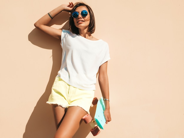 Young beautiful sexy smiling hipster woman in sunglasses.trendy girl in summer t-shirt and shorts.positive female with blue penny skateboard posing in the street near wall Free Photo