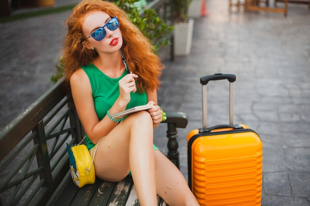 Young beautiful sexy woman, hipster outfit, red hair, traveler, green top, orange suitcase, making notes, travel diary book Free Photo