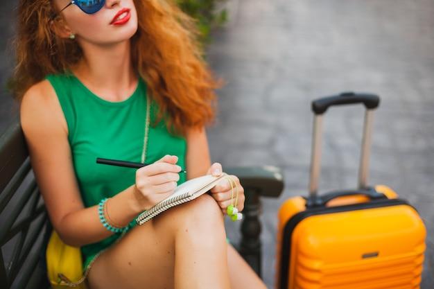 若い美しいセクシーな女性、流行に敏感な服、赤い髪、旅行者、緑のトップ、オレンジ色のスーツケース、メモ、旅行日記の本 無料写真