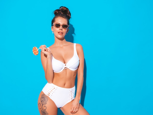Young beautiful sexy woman with ghoul hairstyle. trendy girl in casual summer white swimsuit in sunglasses.hot model isolated on blue.eating,biting candy lollipop Free Photo