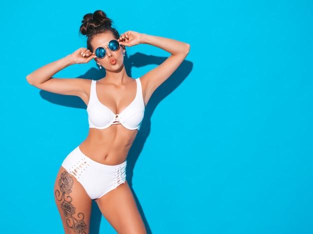 구울 헤어 스타일을 가진 젊은 아름 다운 섹시 한 여자. 선글라스에 캐주얼 여름 흰색 수영복 유행 소녀. 블루에 고립 된 핫 모델입니다. 오리 얼굴 무료 사진