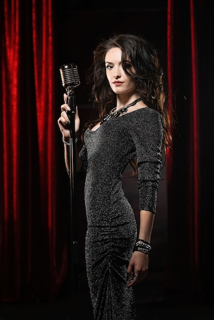 Young beautiful singer in black dress posing with microphone Premium Photo