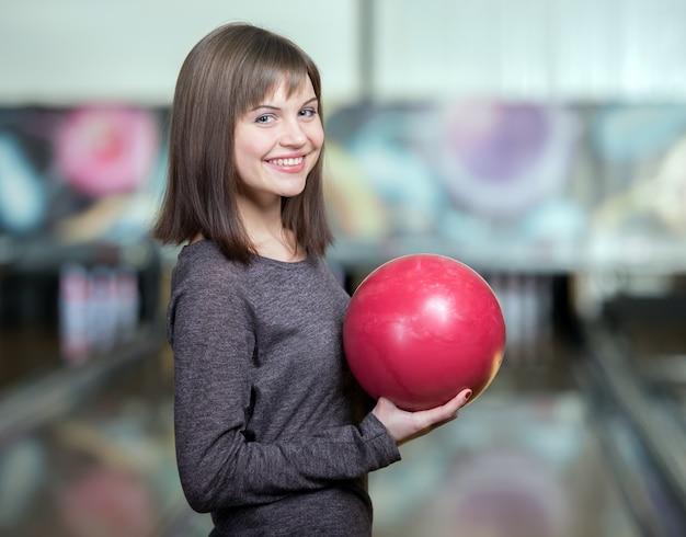 Young beautiful smiling girl playing bowling. Premium Photo