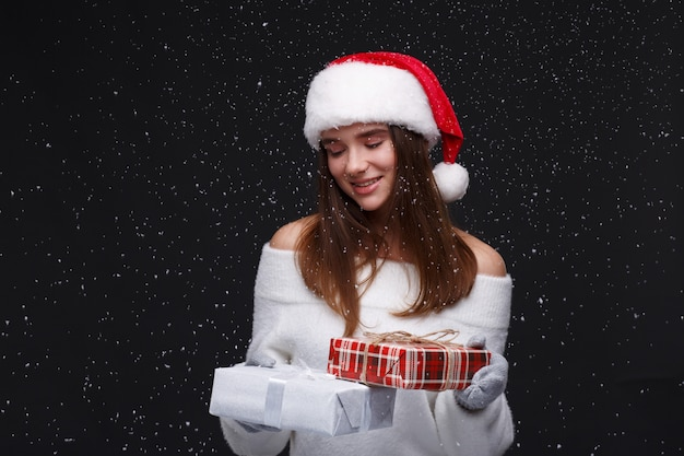 Young beautiful smiling girl in red santa hat holding gift boxes Premium Photo