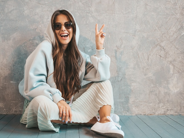 Young beautiful smiling woman looking . trendy girl in casual summer hoodie and skirt clothes. funny and positive female in sunglasses sitting on the floor and showing peace sign Free Photo