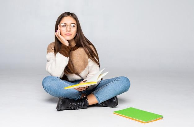 Молодой красивый студент, сидя с книгой, чтение, обучение. изолированные на белой стене Бесплатные Фотографии