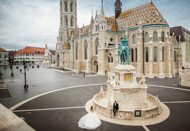 Young beautiful stylish pair of newlyweds walking by the fisherman's bastion in budapest, hungary. top view Premium Photo