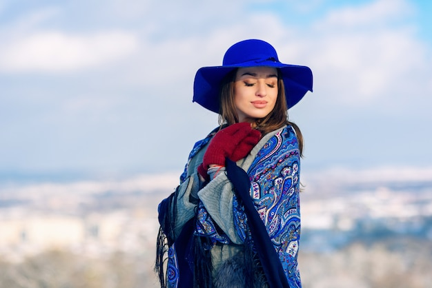 Young beautiful stylish woman in blue hat and scarf walking in the park Premium Photo