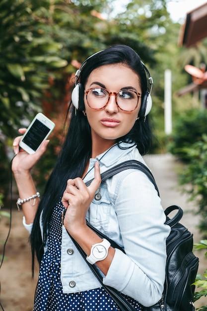 Giovane bella donna elegante che utilizza smartphone, cuffie, occhiali da vista, estate, vestito di denim vintage, sorridente, felice, positivo Foto Gratuite