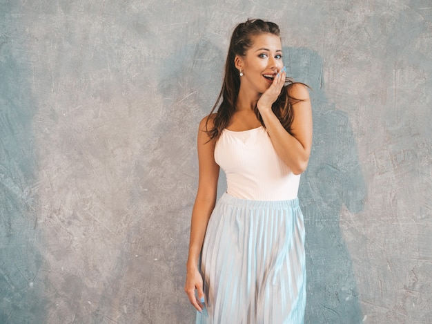 Young beautiful surprised woman looking  with hands near face. trendy girl in casual summer clothes. female posing near gray wall Free Photo