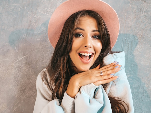 Young beautiful surprised woman looking  with hands near mouth. trendy girl in casual summer clothes and hat. female posing near gray wall Free Photo