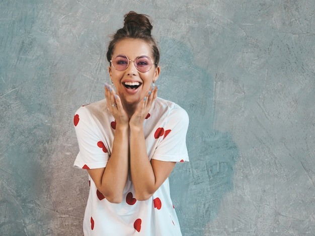 Young beautiful surprised woman looking  with hands near mouth. trendy girl in casual summer white dress. Free Photo