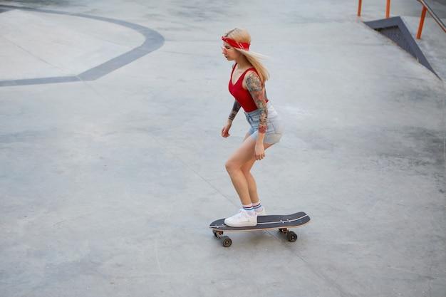 Молодая красивая татуированная дама со светлыми волосами в красной футболке и джинсовых шортах, с вязанной банданой на голове, наслаждается днем и совершает набег на скейтборде в скейт-парке. Бесплатные Фотографии
