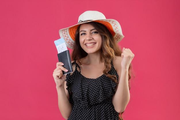 Ragazza giovane bella viaggiatore in vestito a pois in valigia di biglietti aerei cappello estivo guardando uscito e felice alzando il pugno gioendo del suo successo e vittoria in piedi su sfondo rosa Foto Gratuite