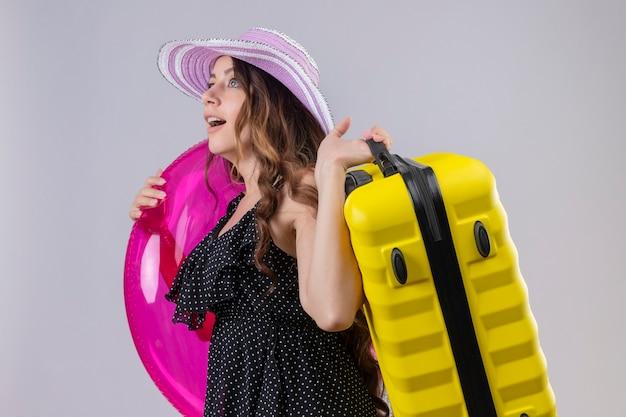 Молодая красивая девушка путешественника в платье в горошек в летней шляпе держит надувное кольцо и чемодан, глядя удивленно и изумленно стоя на белом фоне Бесплатные Фотографии