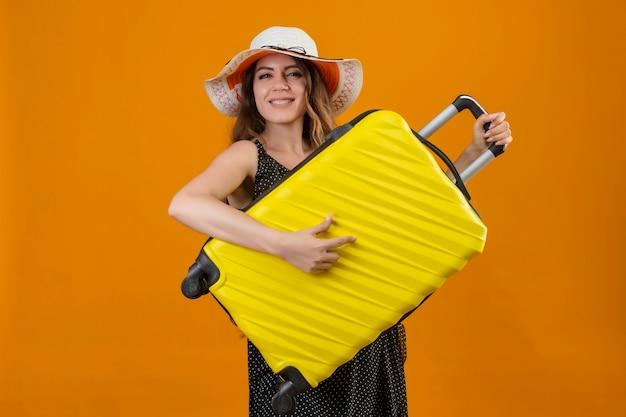 Молодая красивая девушка путешественника в платье в горошек в летней шляпе держит чемодан, используя в качестве гитары, веселится, радостно и счастливо стоя на желтом фоне Бесплатные Фотографии