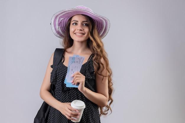 Молодая красивая девушка путешественника в летней шляпе с рюкзаком, держащим авиабилеты, весело улыбаясь, счастливо и позитивно стоя на белом фоне Бесплатные Фотографии