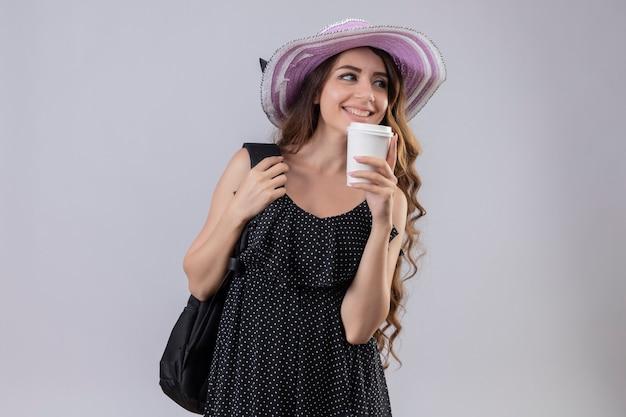 Молодая красивая девушка путешественника в летней шляпе с рюкзаком, держа чашку кофе, весело улыбаясь и позитивно глядя в сторону, стоя на белом фоне Бесплатные Фотографии