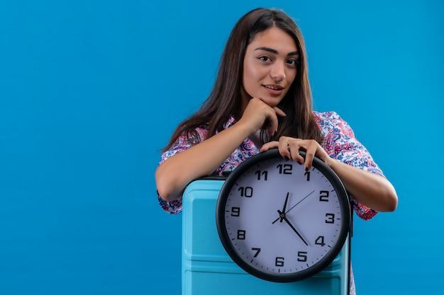 Молодая красивая женщина путешественника держа голубой чемодан и круглые часы с рукой на подбородке думая и ждать над голубой стеной Бесплатные Фотографии