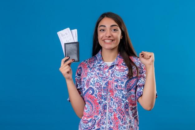 分離された青い壁を越えて休日に準備ができて、勝利後に拳を上げる陽気に笑顔のチケットでパスポートを保持している若い美しい旅行者女性 無料写真