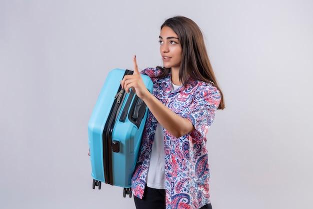 白い壁を越えて顔にスーツケースジェスチャーを保持している若い美しい旅行者の女性の顔に深刻な自信を持って式を待つ 無料写真