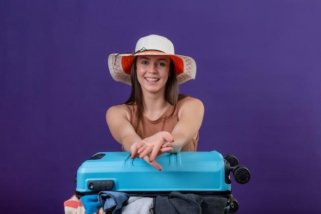Молодая красивая женщина-путешественница в летней шляпе с чемоданом, полным одежды, оптимистично и счастливо смотрит в камеру с улыбкой на лице, стоя на фиолетовом фоне Бесплатные Фотографии