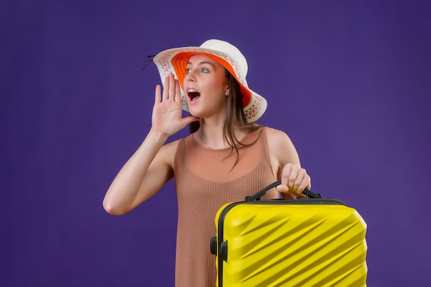Young beautiful traveler woman in summer hat with yellow suitcase shouting or calling someone with hand near moth over purple wall Free Photo