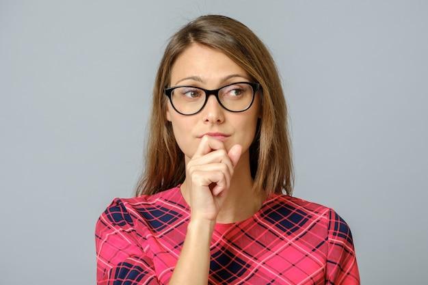Молодая красивая с рукой на подбородке думает о вопросе Premium Фотографии