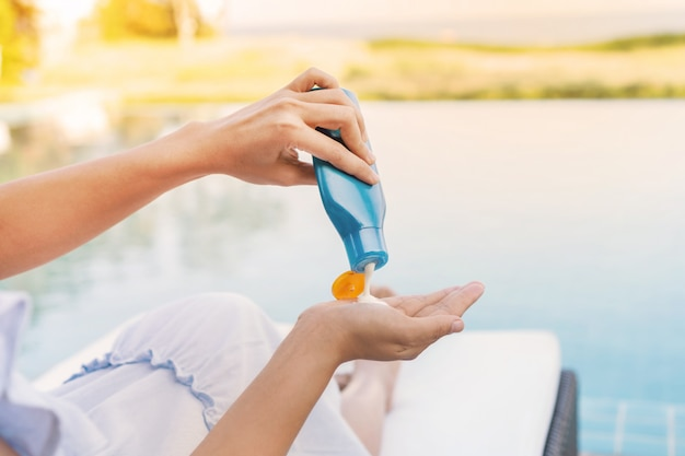 Young beautiful woman applying sunscreen or suntan lotion in her body for solar skin protection at swimming pool, summer holidays concept. Premium Photo