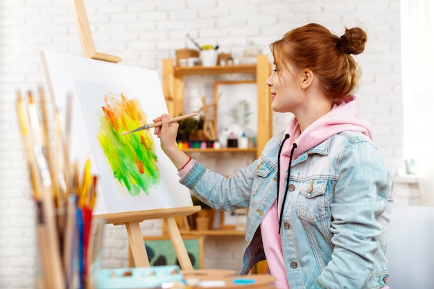Young beautiful woman artist drawing abstract painting on an easel Premium Photo