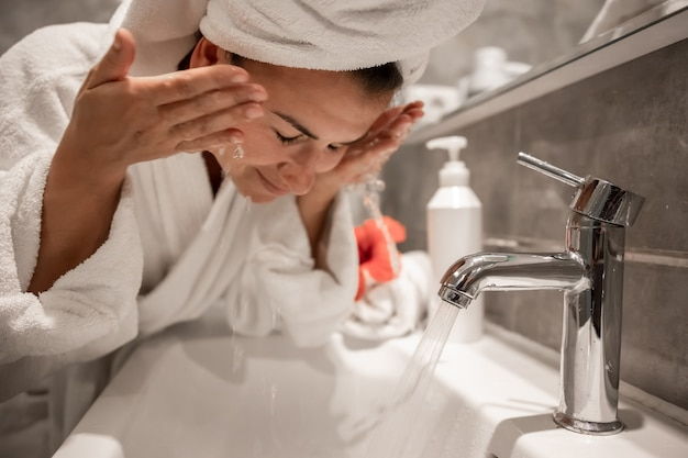 Young beautiful woman in the bathroom with a towel on her head washes her face with tap water Free Photo