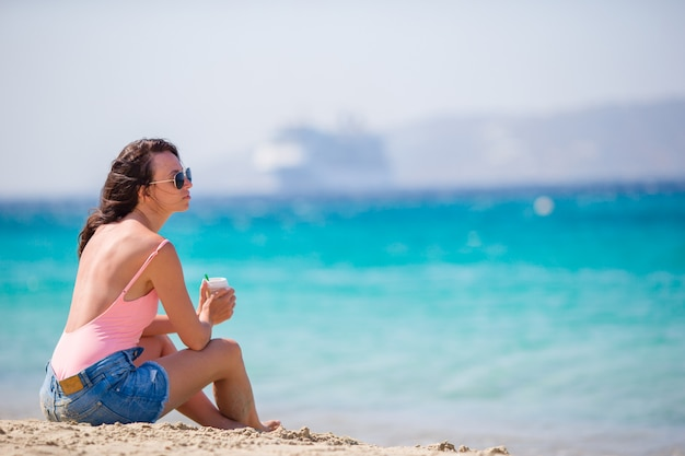 Young beautiful woman on the beach in europe. girl with coffee on vacation in mykonos, greece Premium Photo