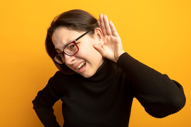 Young beautiful woman in a black turtleneck and glasses holding hand near her ear trying to listen gossips standing over orange wall Free Photo
