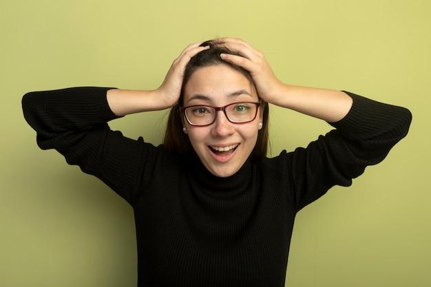 Giovane bella donna in un dolcevita nero e occhiali guardando davanti pazzo felice mano nella mano sulla sua testa in piedi sopra la parete chiara Foto Gratuite