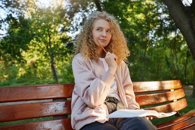 A young beautiful woman blonde sits on a park bench, with headphones and notepad, looks away Free Photo
