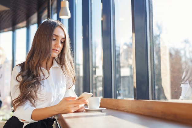 Young beautiful woman in business clothes use smartphone in a cafe Premium Photo