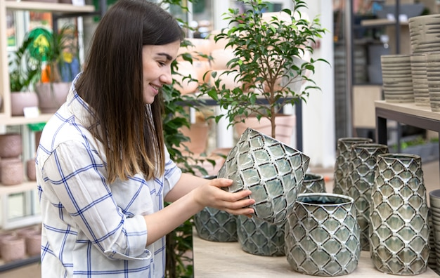 Young beautiful woman chooses a flower pot in a flower shop. Free Photo