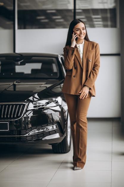 Giovane bella donna che sceglie automobile in una sala d'esposizione dell'automobile Foto Gratuite