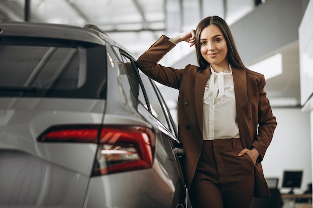 Молодая красивая женщина, выбирая автомобиль в автосалоне Бесплатные Фотографии