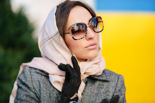 Giovane bella donna in un cappotto che si siede su una panchina nel parco Foto Gratuite