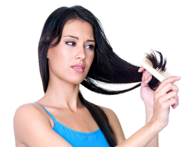 Молодая красивая женщина расчесывает волосы и смотрит на кончики волос - изолированные Бесплатные Фотографии