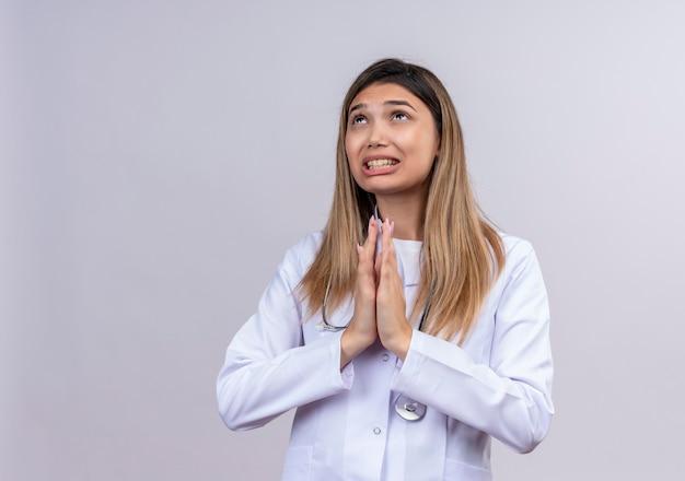 Giovane bella donna medico indossa camice bianco con lo stetoscopio elemosinando e pregando con le mani insieme con l'espressione di speranza sul viso molto emotivo e preoccupato Foto Gratuite