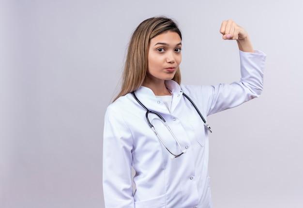 勝者のようにポーズをとって自信を持って拳を上げる聴診器で白衣を着ている若い美しい女性医師 無料写真